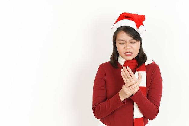 赤のタートルネックと白で隔離のサンタ帽子を身に着けている美しいアジアの女性の手の痛み