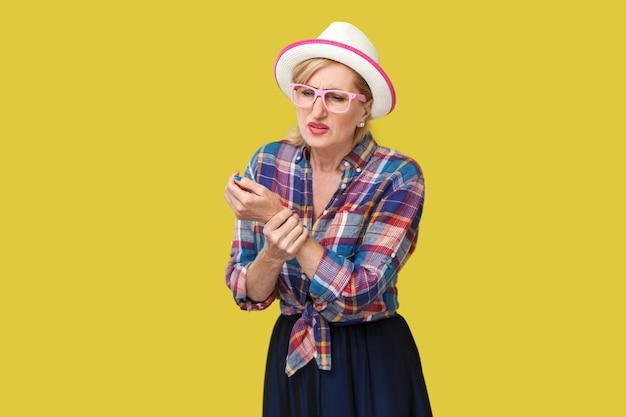 手や手首の痛み。彼女の痛みを伴う手首の手を立って保持している帽子と眼鏡とカジュアルなスタイルの病気のスタイリッシュな成熟した女性の肖像画。黄色の背景に分離された屋内スタジオショット。