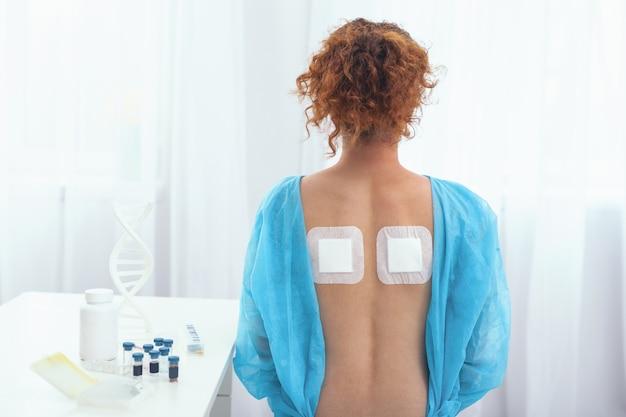 통증 완화. 그녀의 허리 통증이 완화 된 정형 외과 bandaids의 성공적인 사용을 보여주는 labcoat에서 젊은 여자