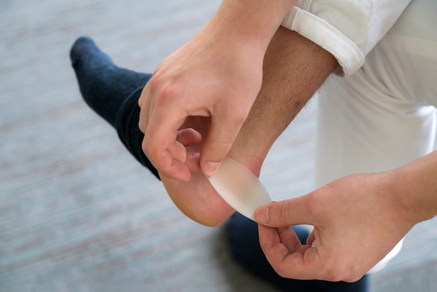 새 신발로 인해 남자의 발에 고통스러운 발 뒤꿈치가 상처를 입었습니다.
