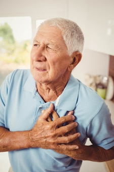 Painful senior man with pain on heart at home