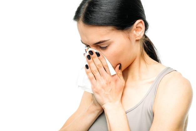 Болезненная женщина с насморком, соплями или гриппом на белом.
