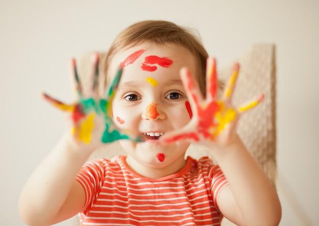 塗られた手を示している女の子。カラフルな絵の具で描かれた手。教育、学校、芸術、painitngのコンセプトです。