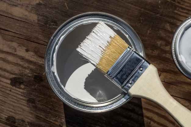 Краска и кисть на деревянном фоне с копией пространства.