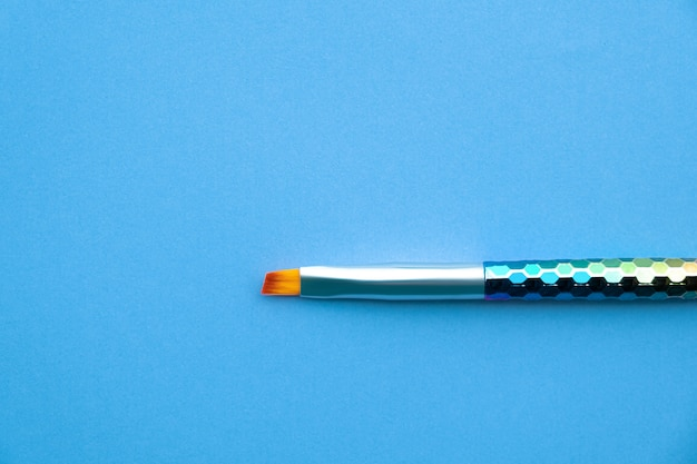 Paint brush on blue paper background.