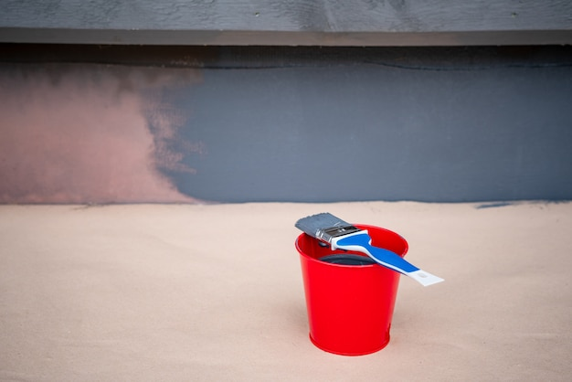 Paint brush and a bucket with paint next to a building wall.