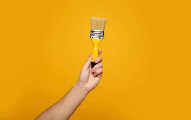 페인트 브러시. 노란색 배경에 페인트 붓을 잡고 손 클로즈업 사진. 홈 리노베이션 개념.