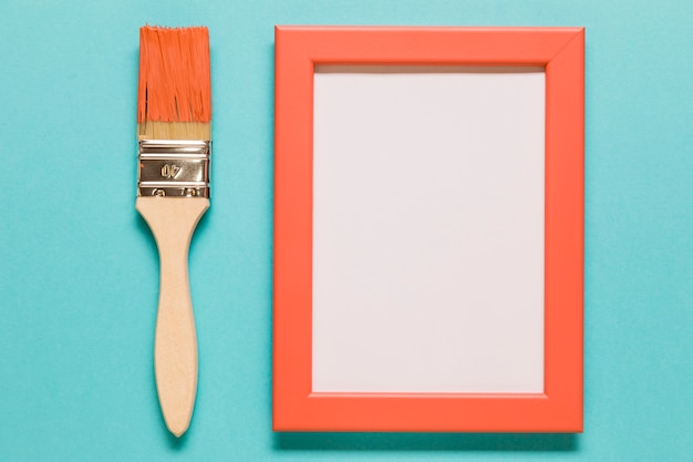 Paint brush and empty frame on blue background