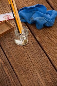 木製のテーブルに水と布で満たされた瓶にブラシをペイントします