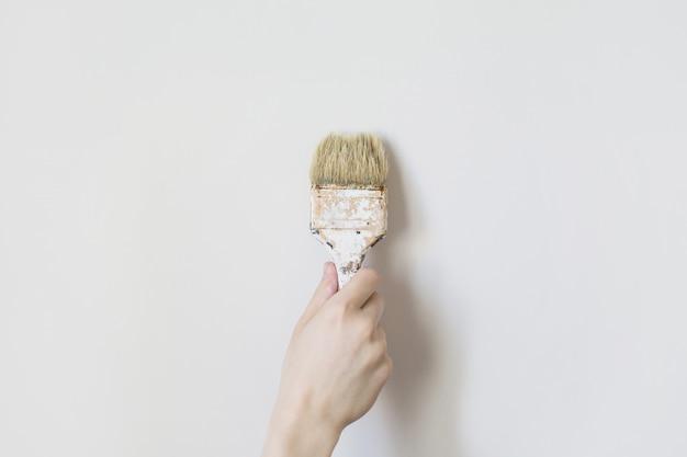 男の手でペイントブラシ。プロセスの概念。男の絵画の壁