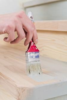수리하는 동안 나무 표면에 페인트를 적용하여 손에 페인트 브러시