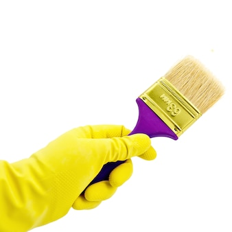 分離された黄色のゴム手袋で手にペイントブラシ