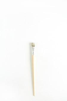 白で隔離されるペイント ブラシ。フラットレイ、トップビューの最小限のコンセプト