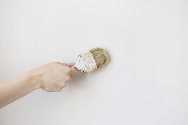 Paint brush in a man's hand on a white background .  process concept. man painting wall illustration, man painting wall image, man painting wall concept
