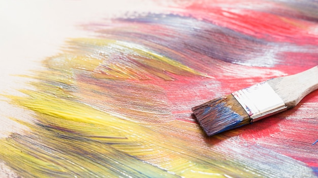 Paint brush on messy colorful brushstroke on surface