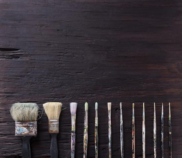 Paint brush on old wood black vintage aged texture background. Premium Photo