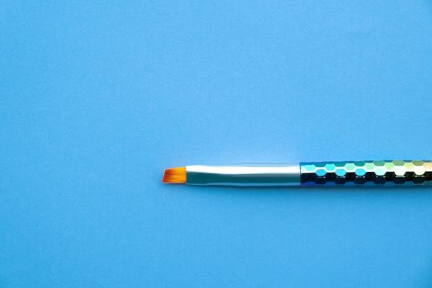 파란 종이 배경에 페인트 브러시입니다.