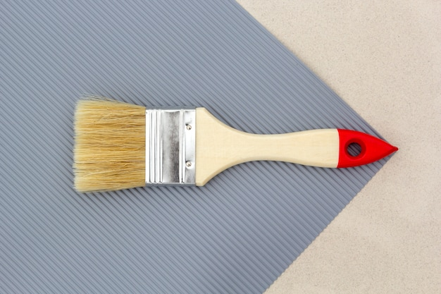 Paint brush for repair on gray. top view.