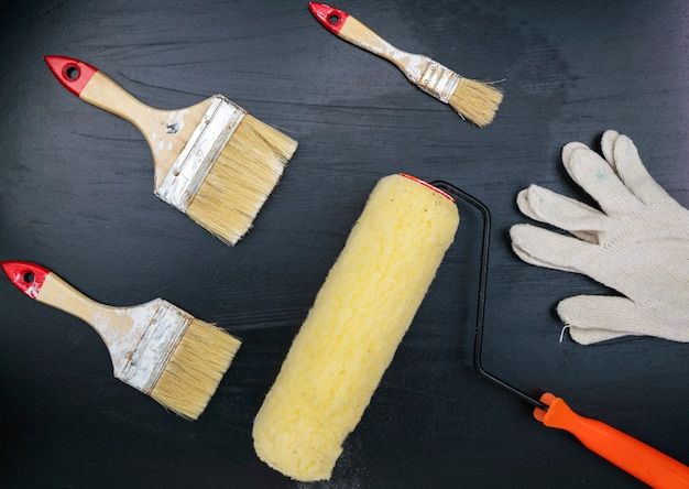 Paint brush and white glove on black background