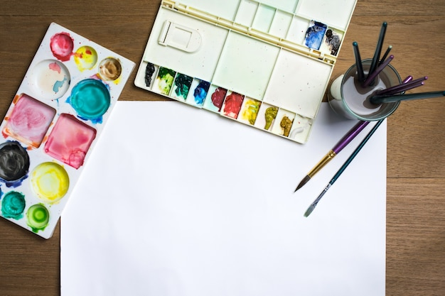 Paint brush on white paper with colorful watercolor and equipment on wooden background.