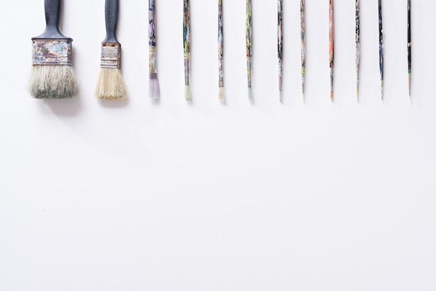 Paint brush on white parchment paper texture background.