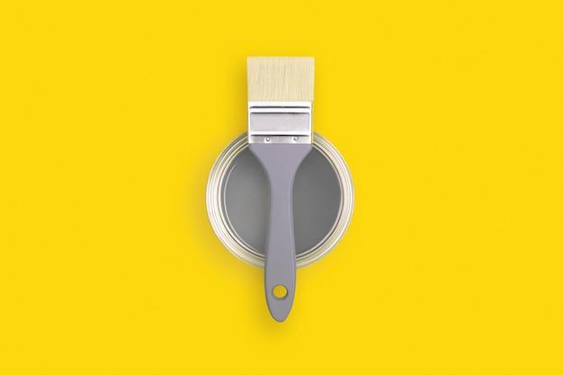 Кисть с открытой банкой краски на модном желтом. освещение и совершенный серый цвет.