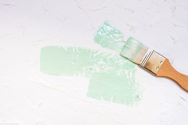 Paint brush with color paint on white wall background