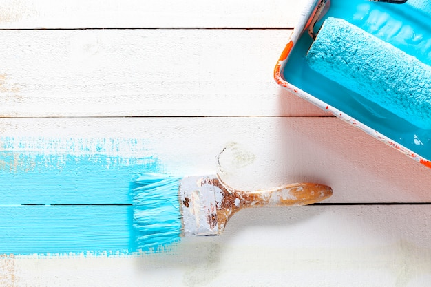 Paint brush with color tray on white wooden background