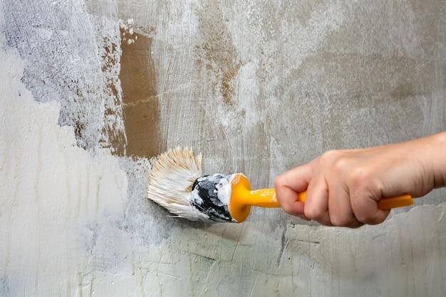 Кисть с желтой пластиковой ручкой в руке художника, перекрашивающего зеленую стену в белый цвет.