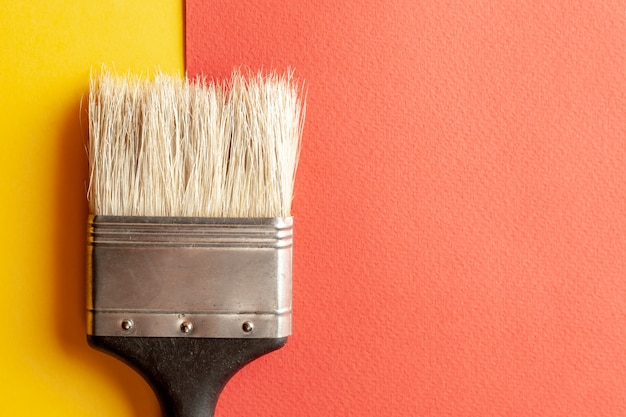 A paint brush at the yellow and red paper background
