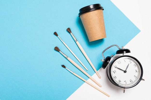Paint brushes, alarm clock and cup of coffee on blue table background.