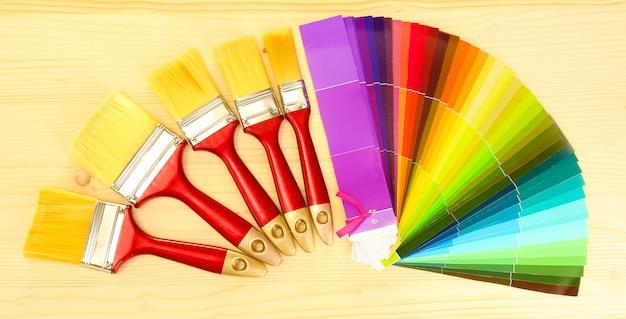 페인트 브러시 및 나무 테이블에 색상의 밝은 팔레트