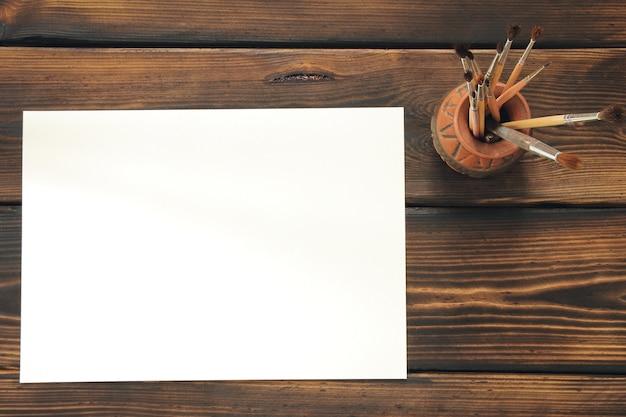 Кисти и бумага на деревянном столе