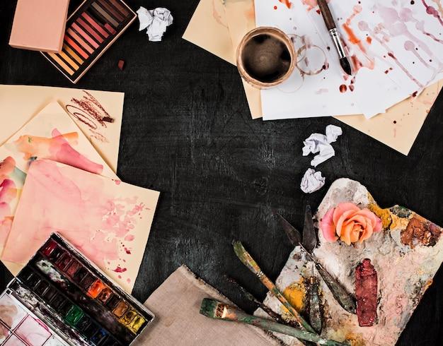 ペイントブラシと木製のテーブルのオイルペイントのチューブ
