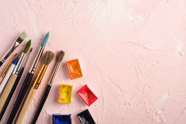 Paint brushes, artist tools for drawing on textured pink background, top view, copy space