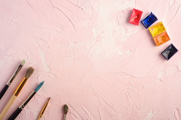Paint brushes, artist tools for drawing on textured pink surface, top view, copy space
