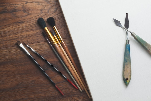 Paint brushes and blank canvas over wooden table