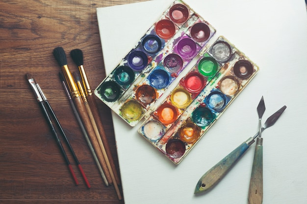 Paint brushes in blank canvas on wooden table
