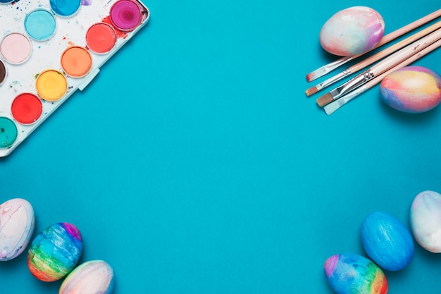 Paint brushes; easter eggs and colorful watercolor box on blue backdrop with space in the center