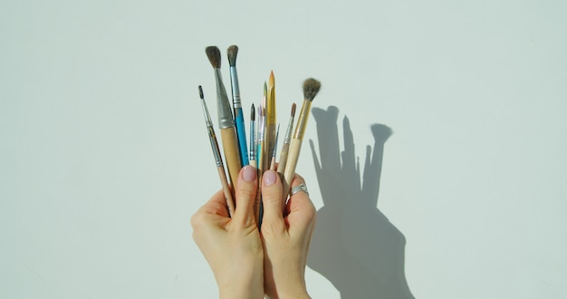 Paint brushes in the hand of painter