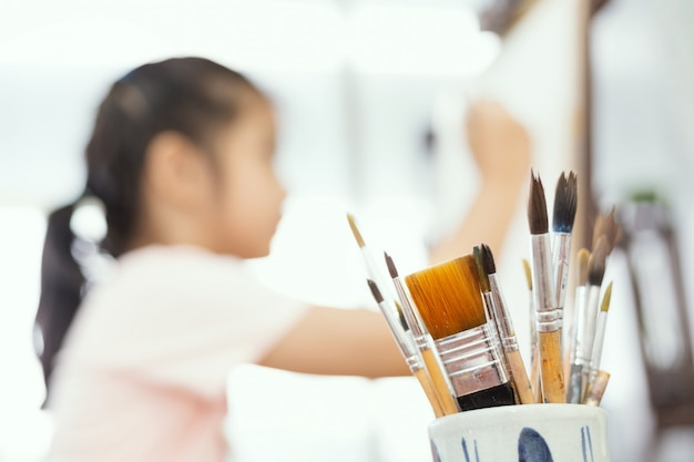 모호한 귀여운 소녀와 함께 항아리에 페인트 브러쉬. 젊은 예술가 소녀.