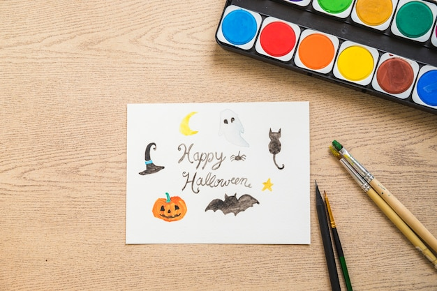 Paint and brushes near halloween drawing
