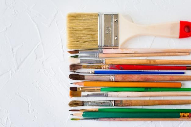 白いテクスチャの背景にさまざまなサイズのブラシと鉛筆をペイントアートと教育オブジェクト