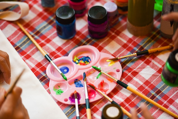 Paint brushes palette and watercolor paints on the table
