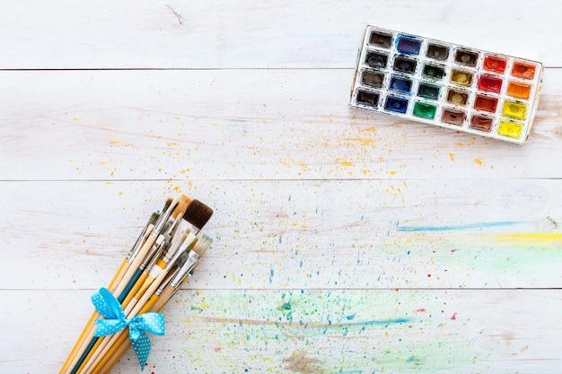 ペイントブラシセットと白い木製のテーブル、トップビューで水彩絵の具でボックス