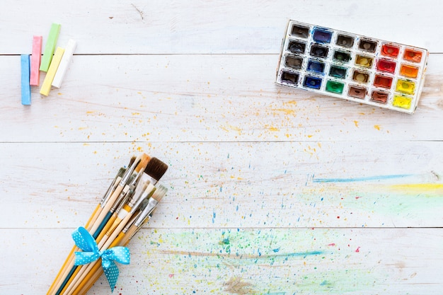 Paint brushes set and box with watercolors on white wooden table, top view