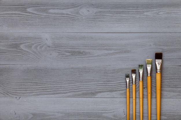 Набор кистей на серый деревянный стол, художественный серый фон