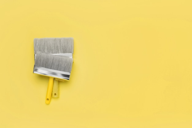 Кисти - вид сверху на желтом. модные 2021 года цвета ultimate grey и illuminating. скопируйте пространство.