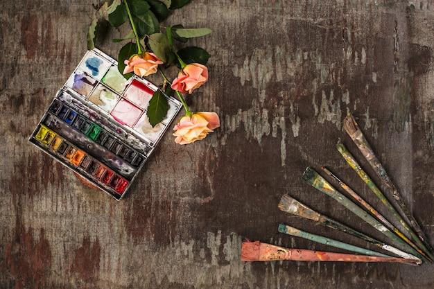 Paint brushes and tubes of oil paints on wood