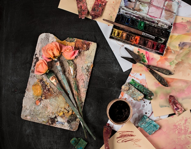 Paint brushes and tubes of oil paints on wooden table
